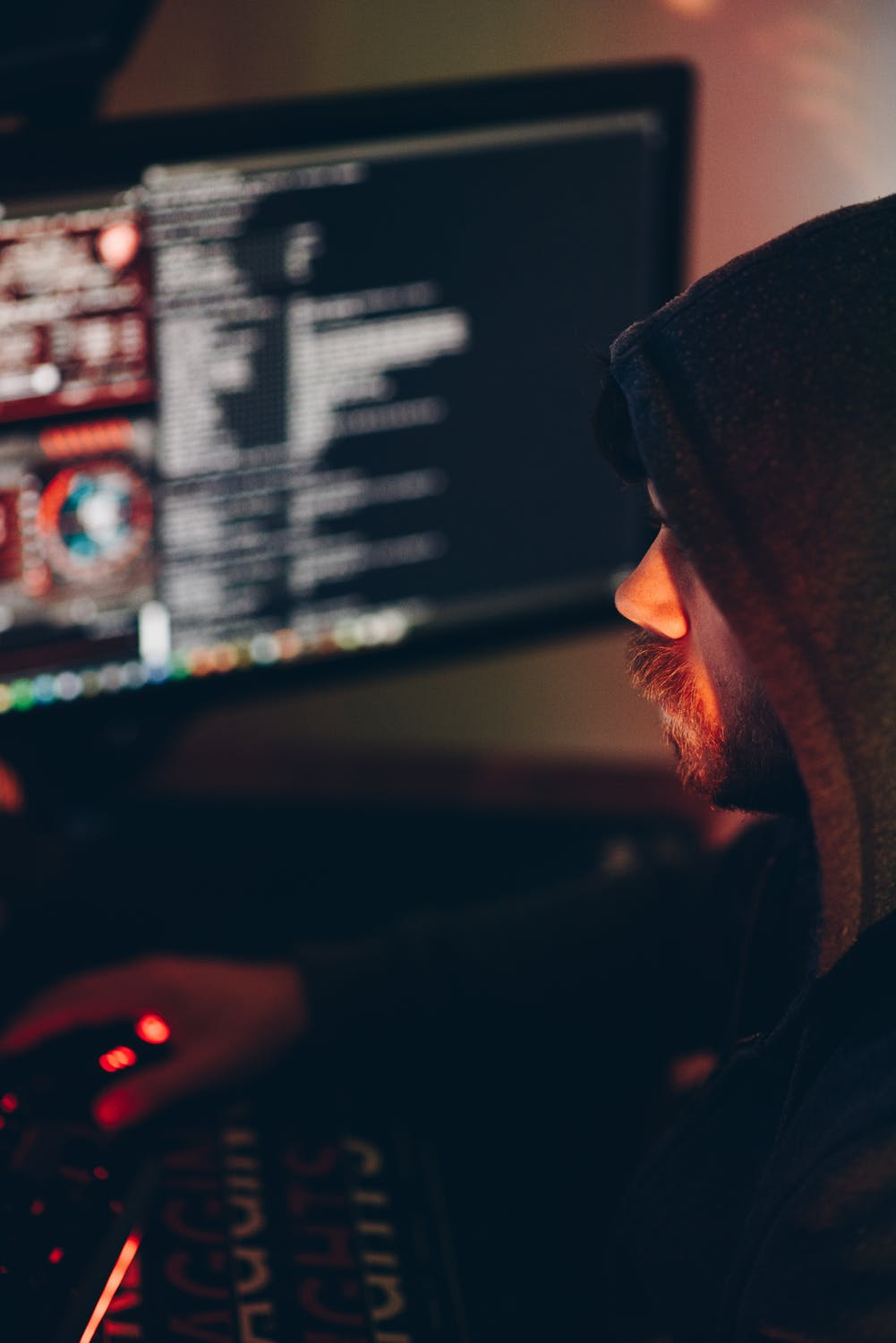 Pros and cons of instagram man in black hoodie on computer with dark lighting