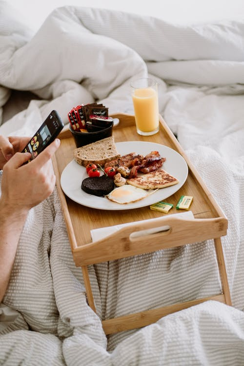Crop person with smartphone and delicious breakfast in bed