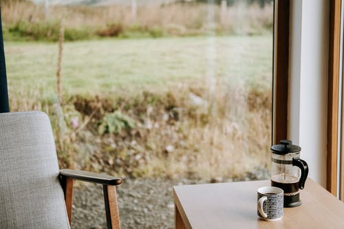 French press with aromatic espresso near ornamental mug on table against glass wall in countryside house