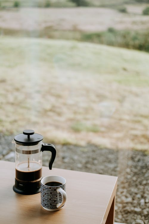 Coffee press near mug with hot drink on table indoors