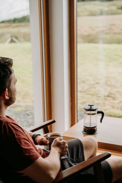 Crop anonymous bearded male with mug of hot drink sitting in armchair against glass wall at home