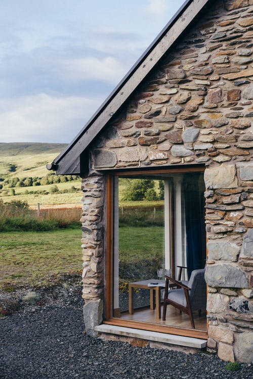 Stone house with glass walls in countryside