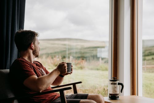 Side view of young dreamy male with mug of hot beverage looking away against glass wall in countryside house