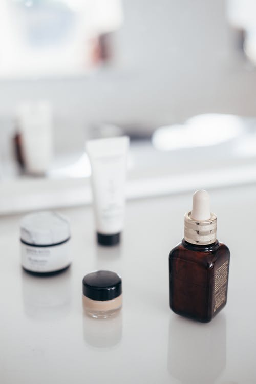 Collection of beauty products on table reflecting in mirror