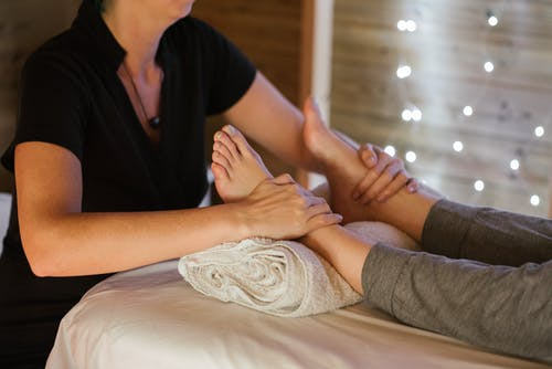 Unrecognizable masseuse therapist giving feet massage to anonymous female client lying on table with legs on towel in spa on blurred background