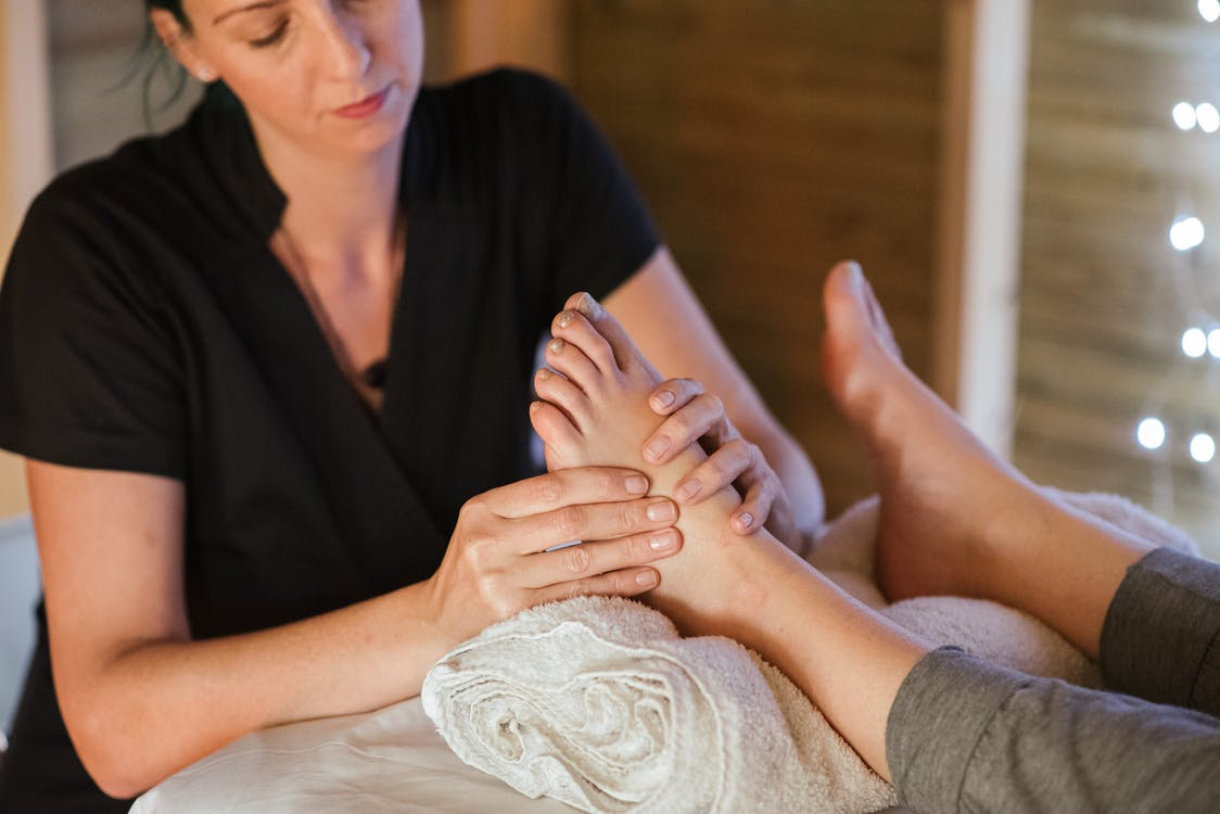 Focused crop woman massaging foot of patient