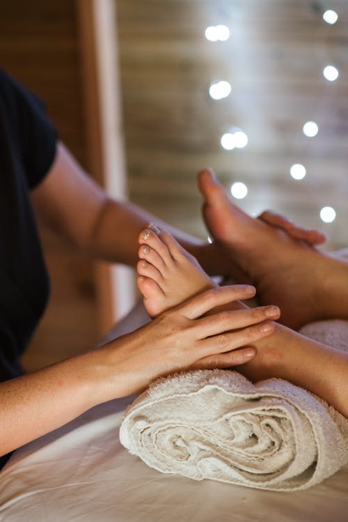 Unrecognizable masseuse kneading feet of unrecognizable female patient lying on table with towel in beauty salon during massage on blurred background