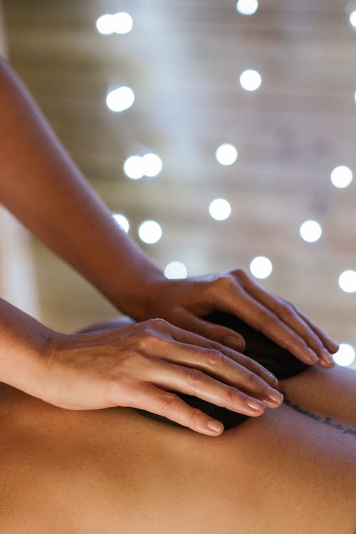 Side view of unrecognizable female specialist massaging back of anonymous patient during hot stone therapy in salon on blurred background