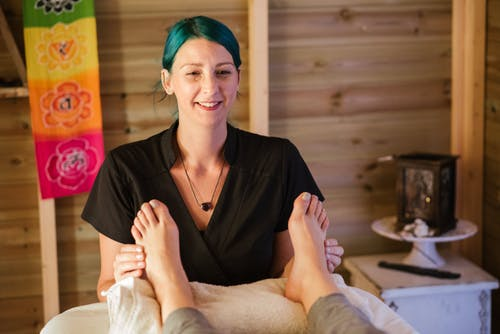 Cheerful female therapist with green hair kneading feet of unrecognizable patient in cozy room with colorful cloth on wooden wall