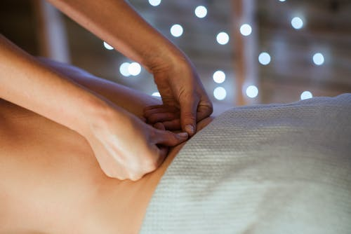 Crop relaxed woman receiving massage