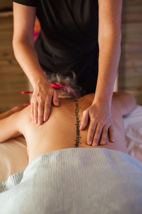 Unrecognizable topless woman getting massage in salon