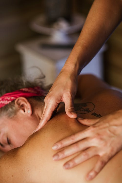 Unrecognizable female client with headband lying topless in spa salon while getting back massage on blurred background during therapy session