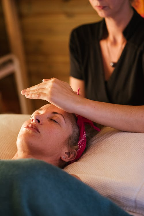 Relaxed woman with closed eyes lying under blanket while getting reiki therapy treatment from unrecognizable therapist in cozy salon with blurred background