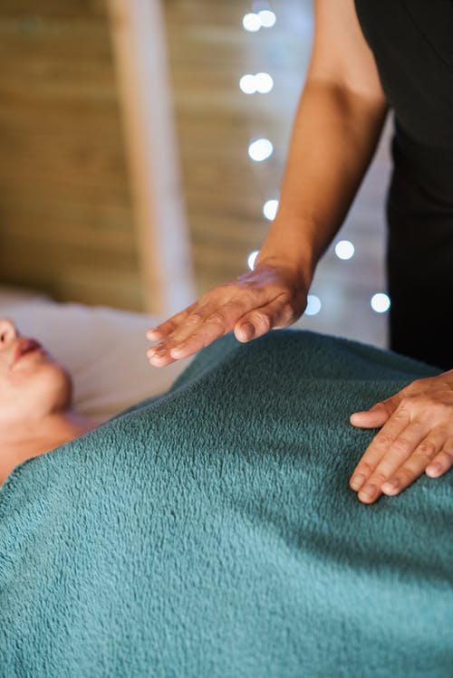 Faceless adult female having massage in towel on comfortable couch in spa salon