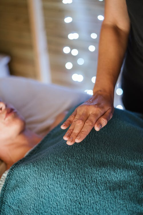 Anonymous adult female in towel having massage on comfortable couch in spa salon