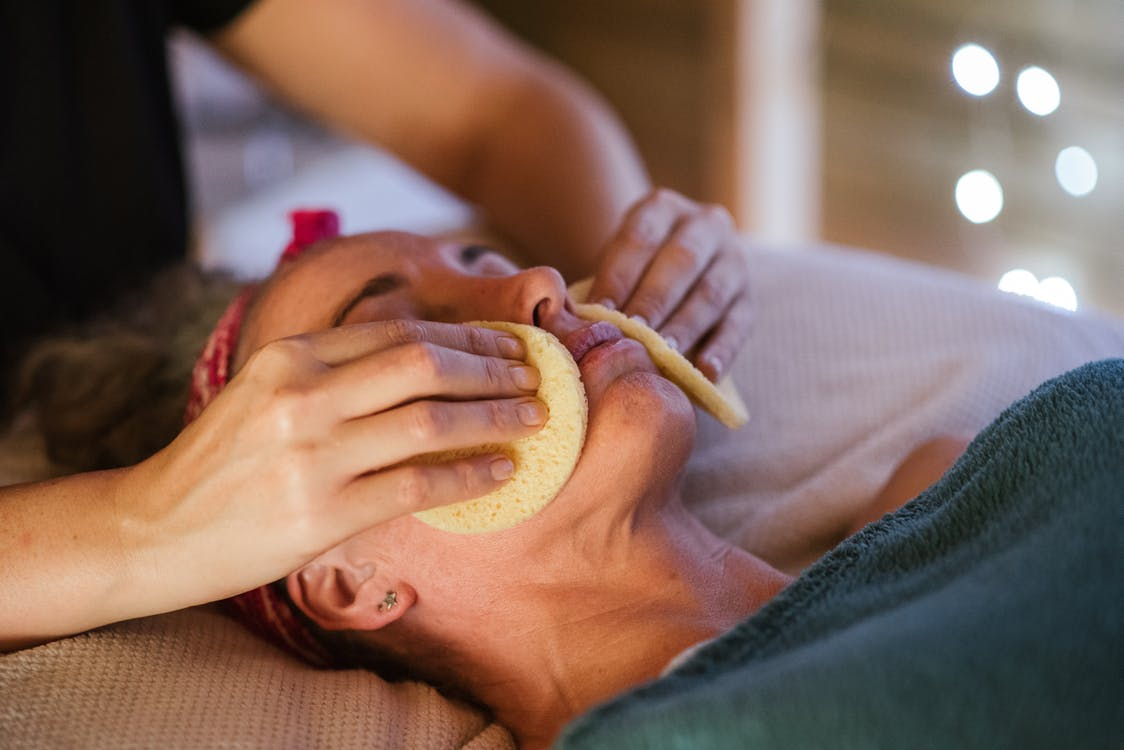 Adult lady in towel getting face massage with sponge from massager in spa