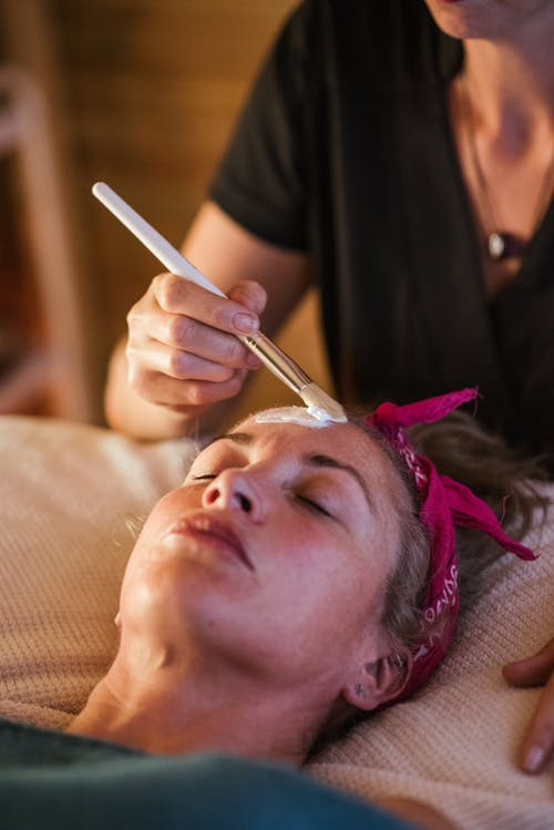 Woman getting mask on massage in spa