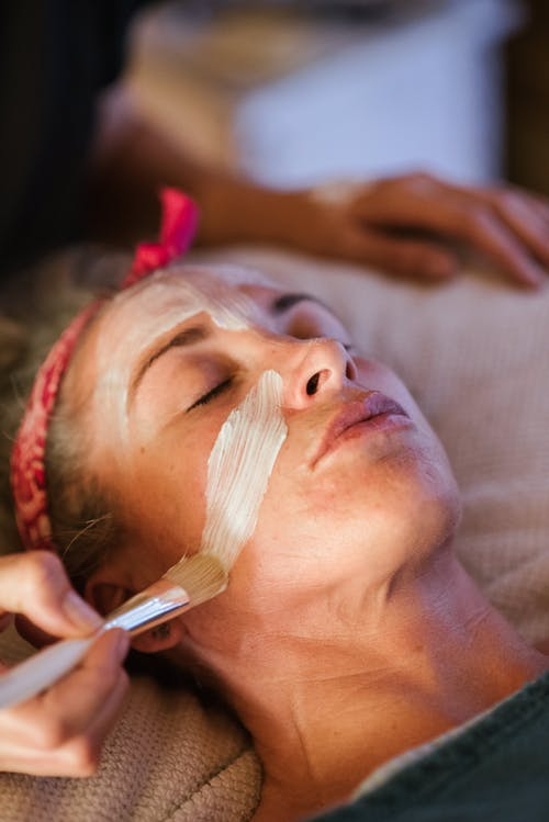 Woman cleaning face with mask in spa center