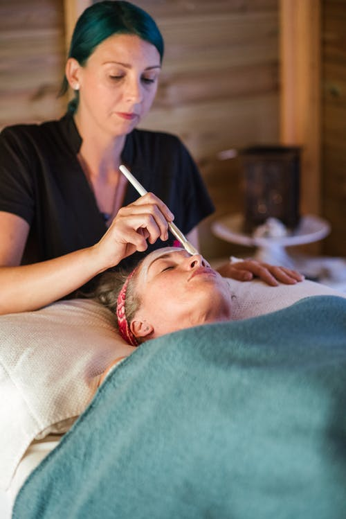 Lady cleaning face with mask in spa salon