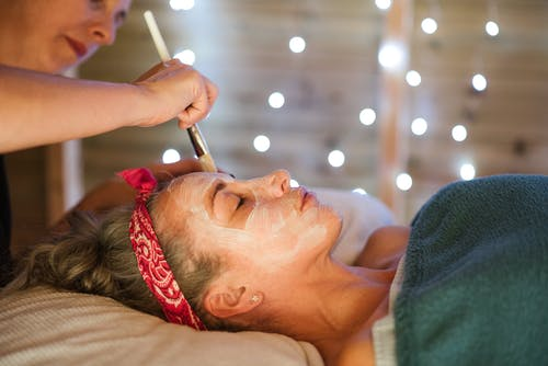 Female applying mask on face in spa