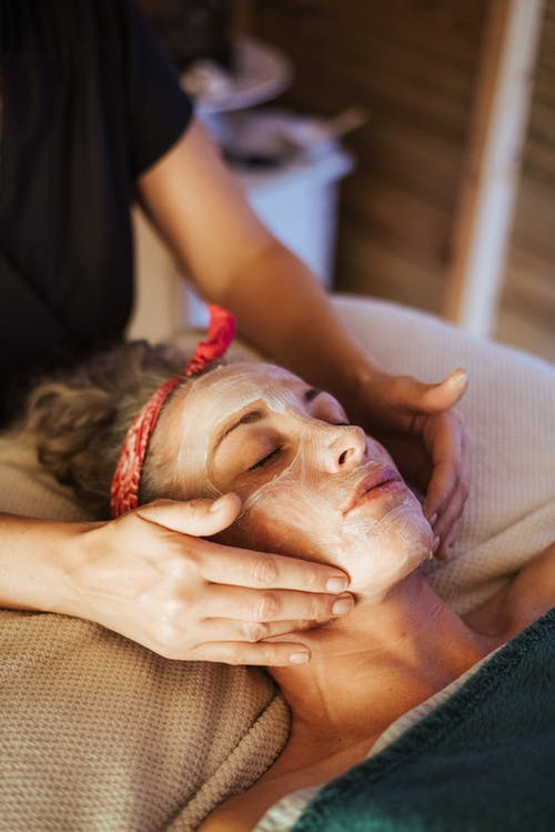 Lady with mask on face doing massage
