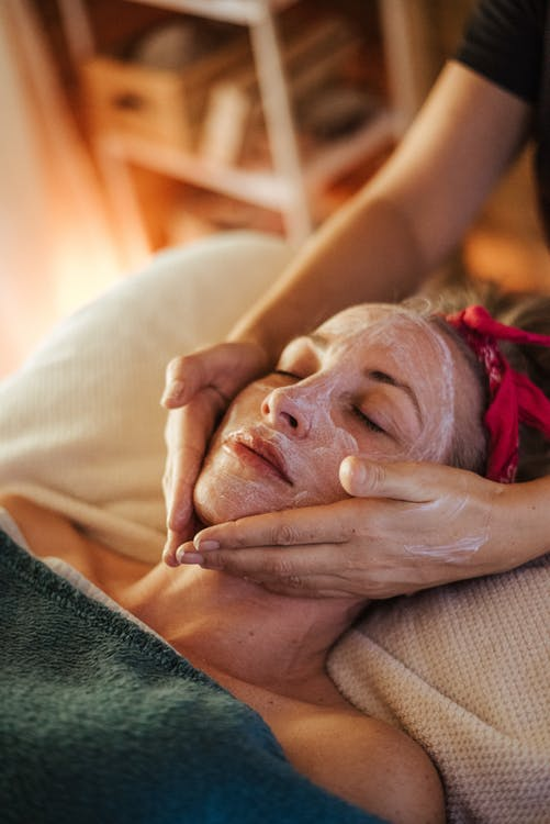 Female doing massage with mask on face