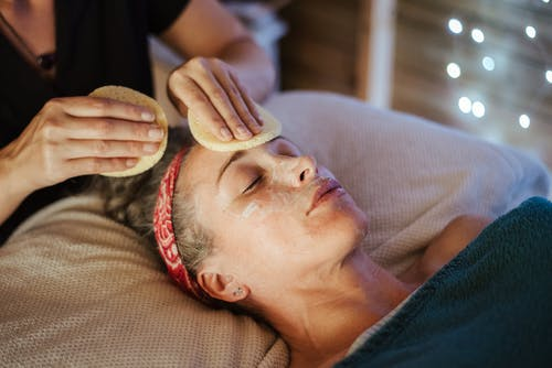 Woman removing mask from face after massage