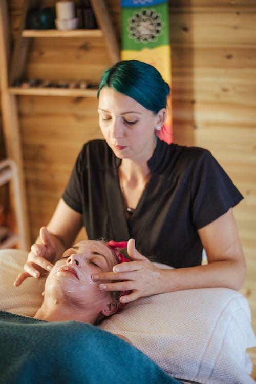 Женщина, наслаждающаяся массажем с маской на лице