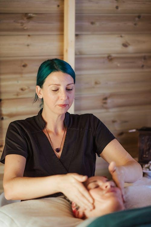 Массажист делает массаж лица даме в спа