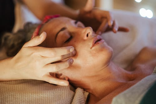 Adult woman relaxing in spa salon on comfortable bed while getting face massage from masseur