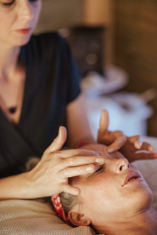Женщина с закрытыми глазами получает массаж в салоне