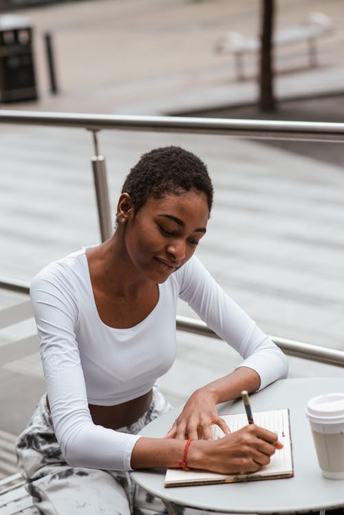 Attractive ethnic woman writing thoughts on terrace