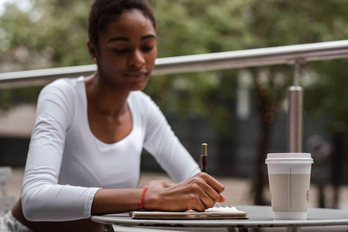 Black woman with coffee and pen on terrace