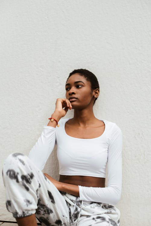 Serious African American female with short hair in trendy outfit sitting with hand on chin and looking away
