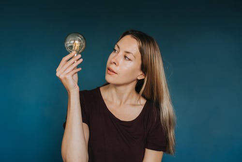 Young woman holding light bulb in studio