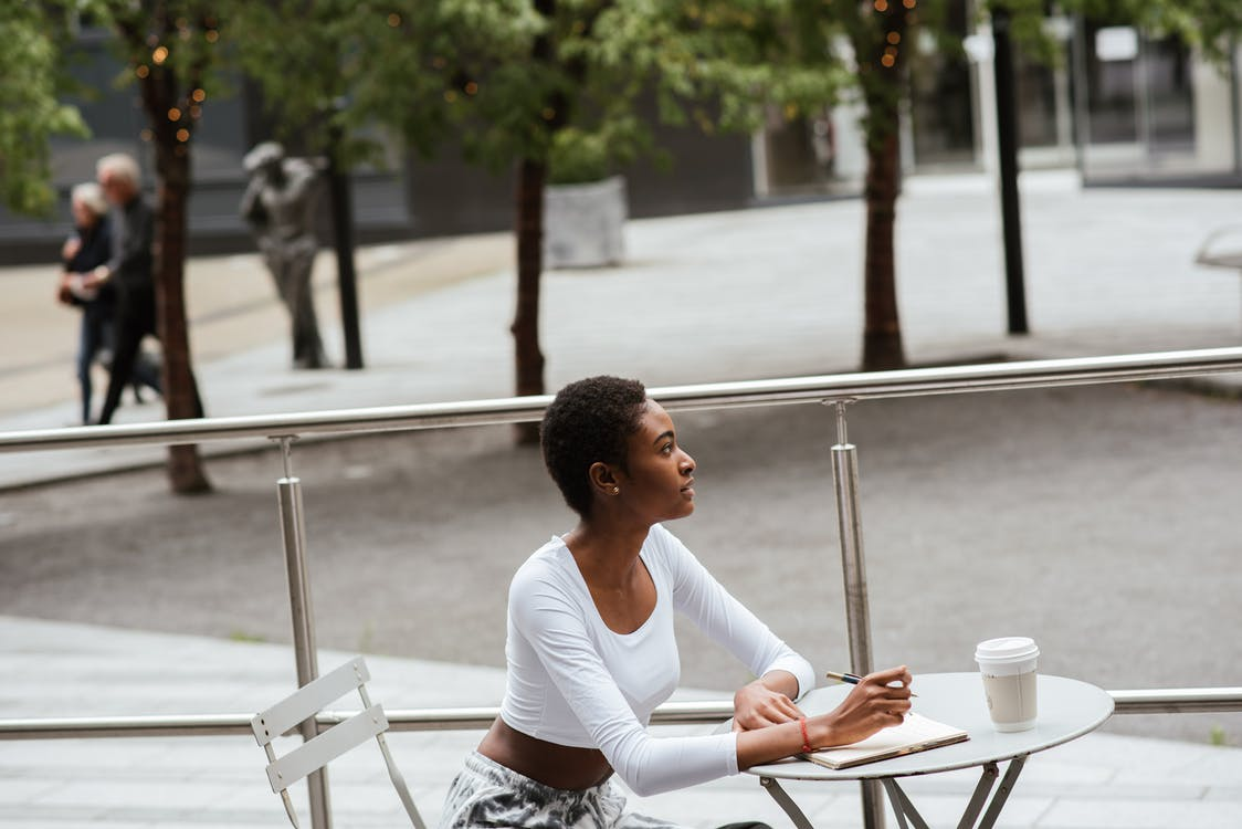 Pensive black woman with coffee and notebook