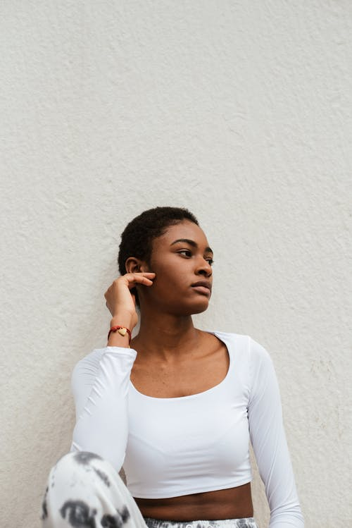 African American female in casual clothes relaxing near wall while touching face and looking away