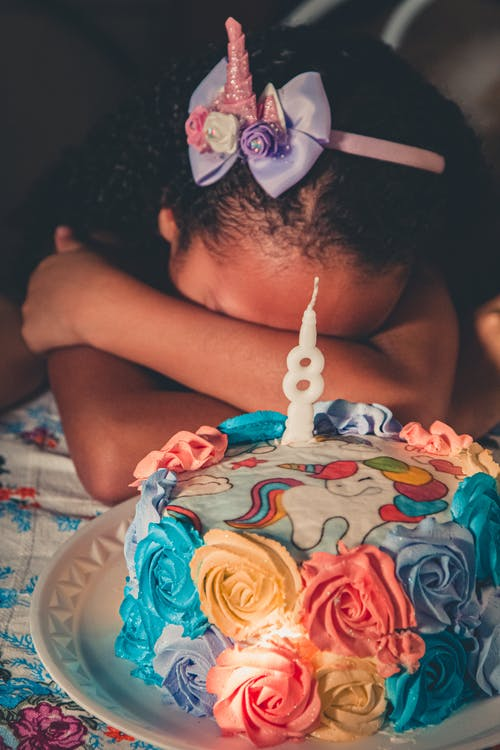 Unrecognizable little African American girl with headband covering face with arms while making wish sitting at table with birthday cake