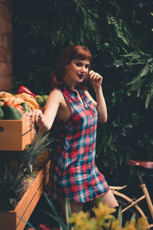 Side view of young eccentric female with ginger hair and dark makeup in checkered dress standing in garden near boxes with assorted fresh vegetables and fruits