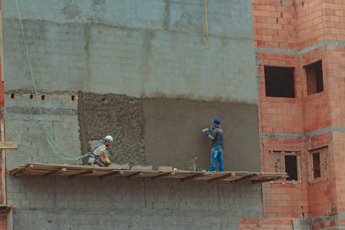 Construction site with builders on brick wall