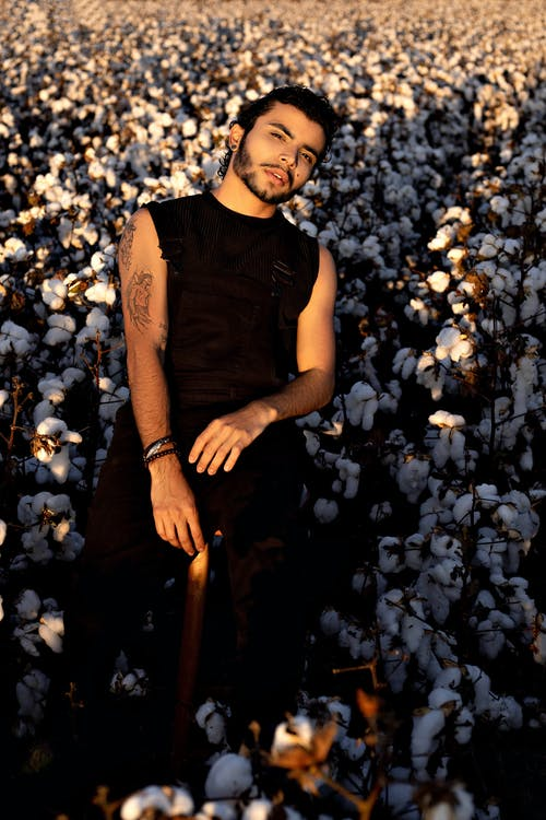 Ethnic young tattooed man in cotton field