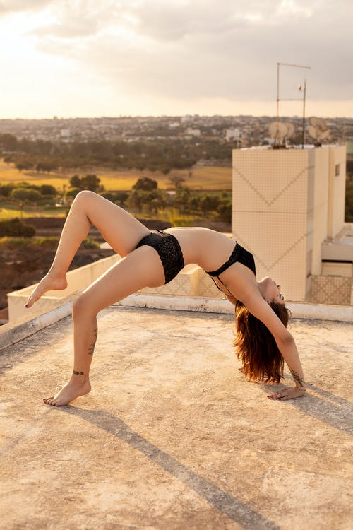 Young flexible woman doing gymnastic on roof