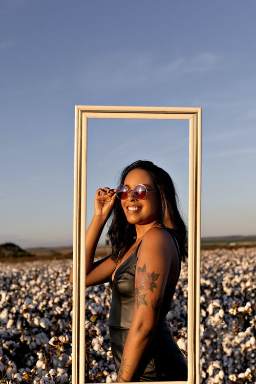 Ethnic tattooed woman in sunglasses smiling in field