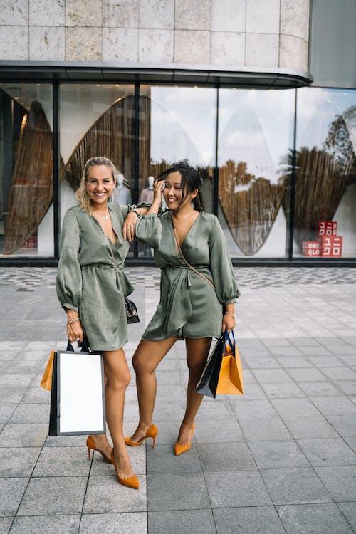 2名穿着灰色衣服的女人站在灰色的水泥地板上