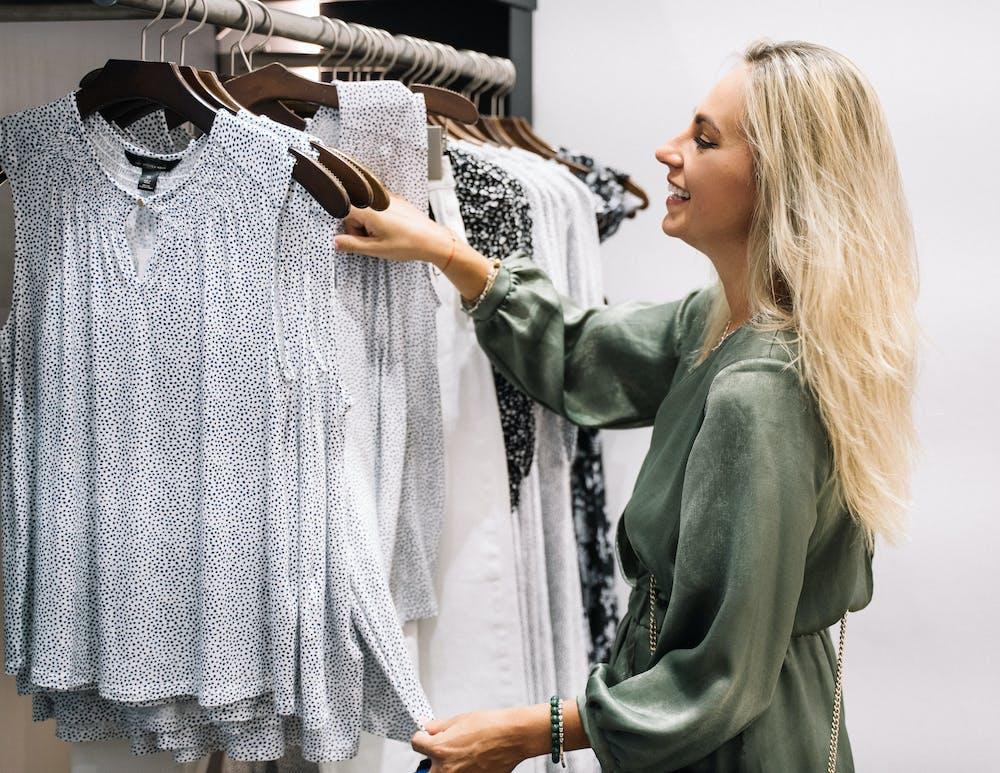 Woman holding clothes hanger.   Photo: Pexels