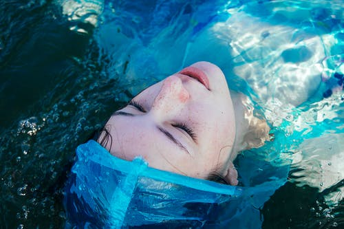 Dead woman in raincoat lying in transparent water