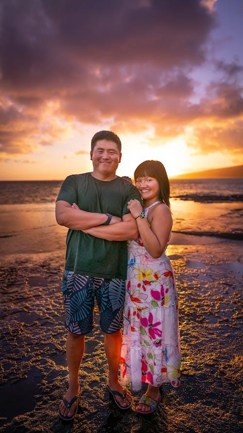 Joyful Asian couple hugging and standing on sunset beach