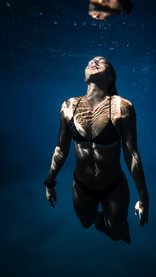 Underwater shot of fit young female in black bikini swimming in dark blue seawater with eyes closed