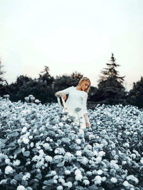 Calm woman in dress standing in blooming garden