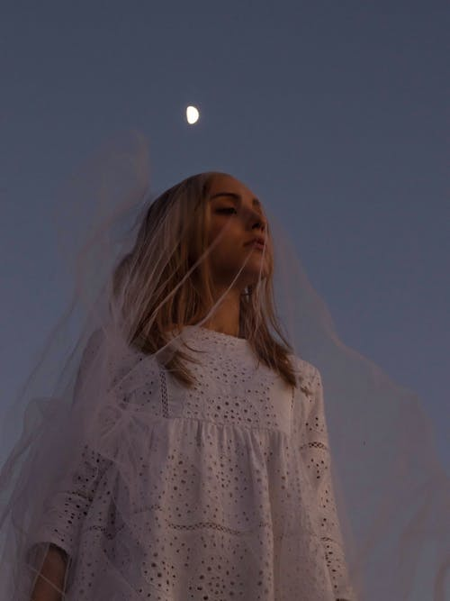 Peaceful woman in veil against moon in darkness
